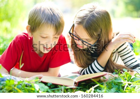 Kids reading together enjoying a book laying on the grass outdoors - stock photo