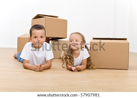 Kids relaxing in their new home with cardboard boxes - stock photo