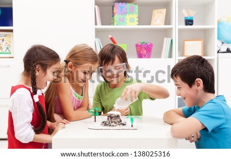 Kids repeating and observing a science lab project at home - the baking soda and vinegar volcano - stock photo