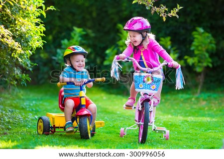 Kids riding bikes in a park. Children enjoy bike ride in the garden. Girl on a bicycle and little boy on a tricycle in safety helmet playing together outdoors. Preschool child and toddler kid biking. - stock photo
