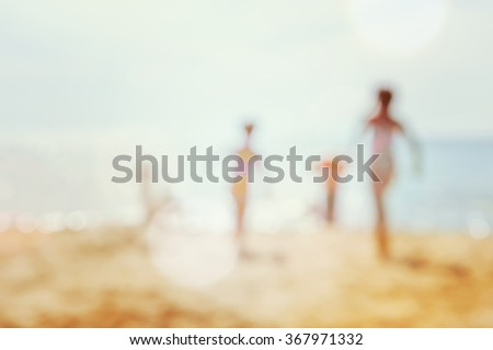kids running at the beach, blurred background image. - stock photo