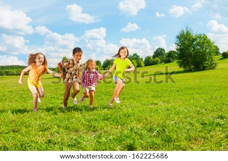 Kids running in the park together 6 and 7 years old, diversity looking, boys and girls running together  - stock photo