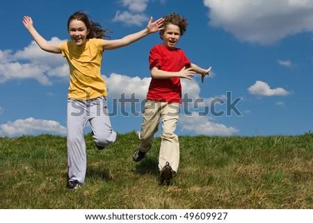 Kids running, jumping against blue sky - stock photo