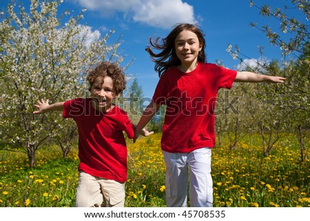 Kids running, jumping outdoor against blue sky - stock photo
