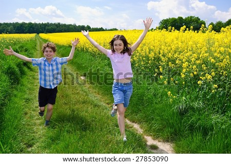 Kids running on green meadow against blue sky - stock photo