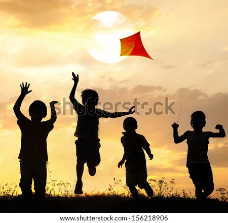Kids running on summer sunset meadow with kite in fresh hot air - stock photo