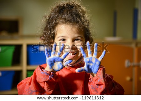Kids, school and education, happy female child having fun and painting in kindergarten, showing hands to camera - stock photo