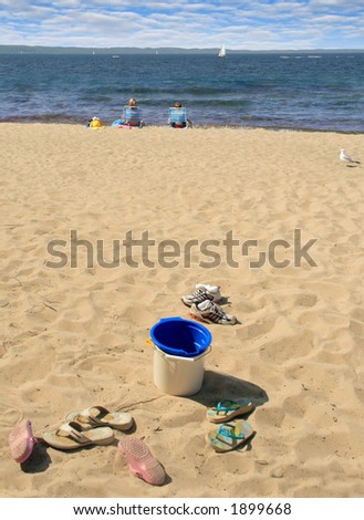 Kids shed their shoes and enjoy the beach - stock photo