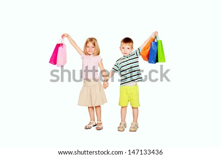 Kids shopping. Young couple, a little boy and a little girl, holding up shopping bags, ready for your text, logo or symbols.. Isolated on white background. - stock photo