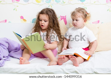 kids sisters reading a book in bed - stock photo