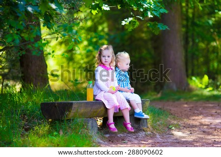 Kids sit on a bench in a park. Children hiking in the forest. Family outdoor fun in summer. Little girl and boy relaxing and drinking juice. Hike with toddler child. Preschooler kid on a day trip. - stock photo