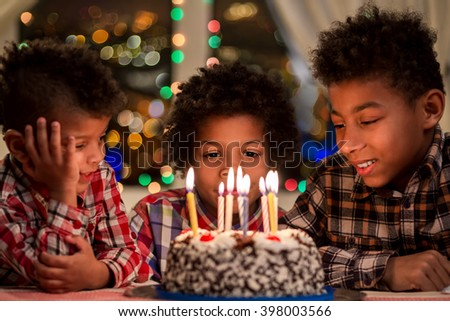 Kids sitting beside birthday cake. Boys near cake with candles. Birthday table beside window. Hurry up, it's night already. - stock photo