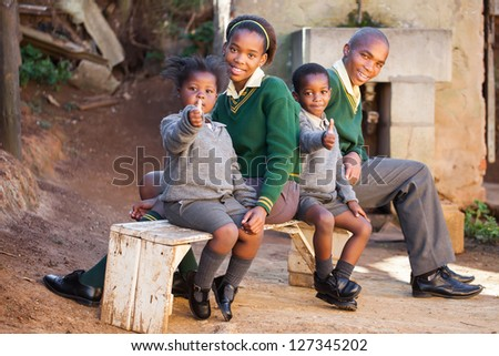 Kids sitting on a bench waiting for the school bus.