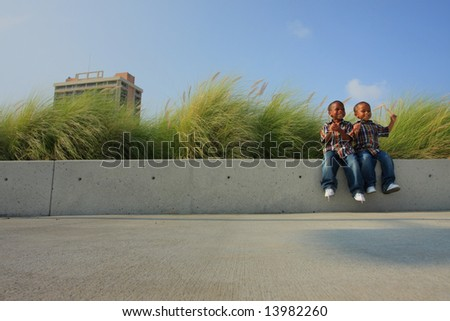 Kids Sitting on a Ledge to the Right - stock photo