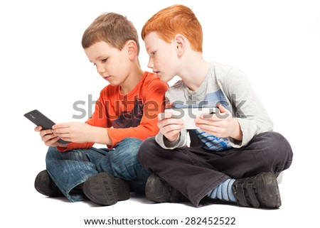 kids sitting playing on mobile phones together