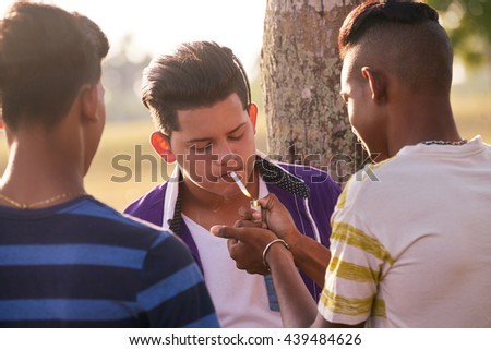 Kids smoking cigarette in park. Concept of health problems and social issues between young people - stock photo