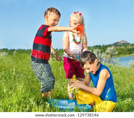 Kids splashing water in the meadow - stock photo