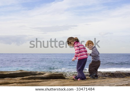 Kids stepping in rock pools with ocean background
