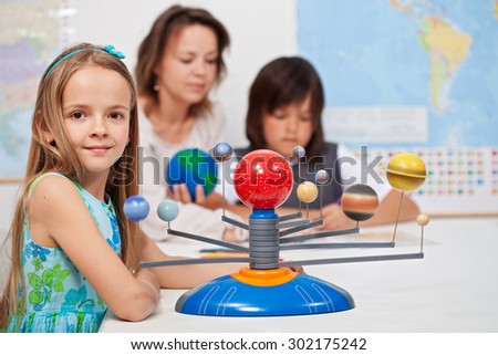 Kids study the solar system under their teacher supervision - focus on the little girl in front - stock photo