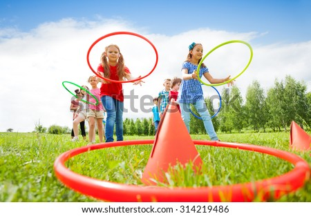 Kids throw colorful hoops on cones while competing - stock photo