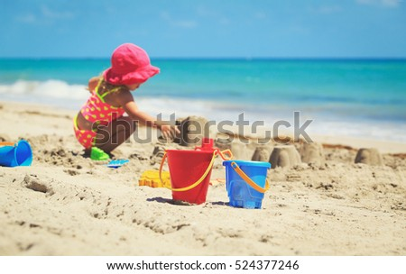 kids toys and little girl playing on the beach