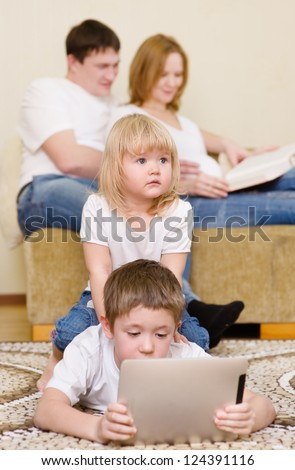 kids using a tablet computer near parents in home - stock photo