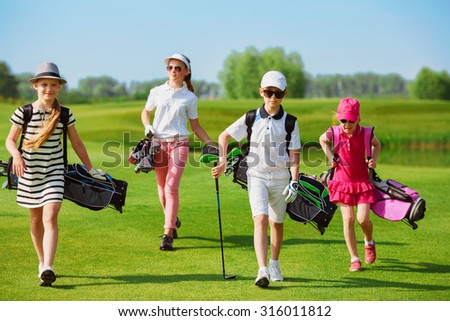 Kids walking on fairway with bags at golf school  - stock photo