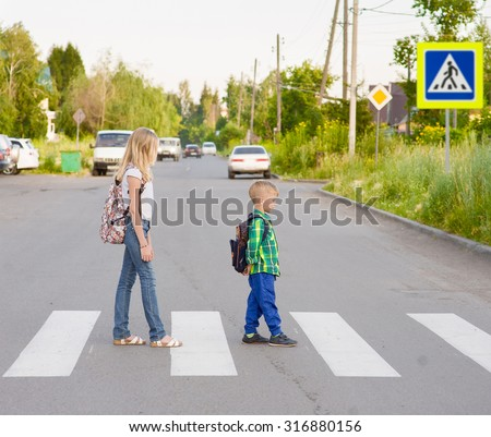 kids walking on the pedestrian crossing - stock photo