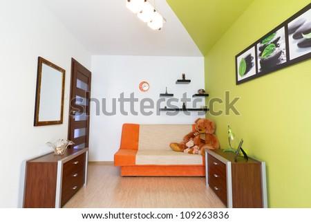 Kids white and green bedroom with orange sofa - stock photo