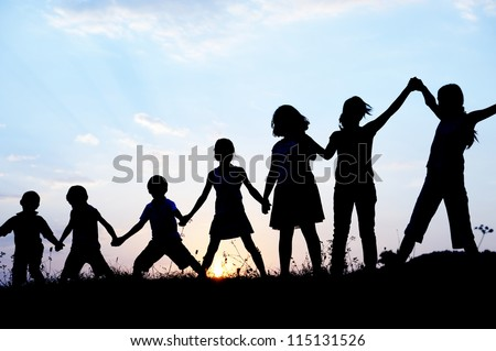 Kids with arms up together in nature - stock photo