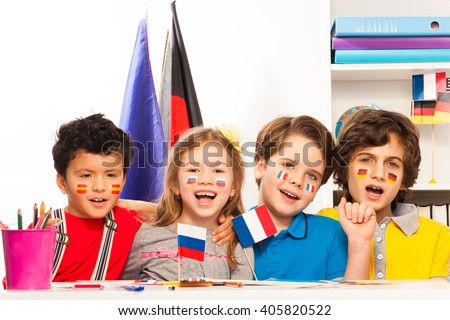 Kids with flags on cheeks singing at the classroom - stock photo