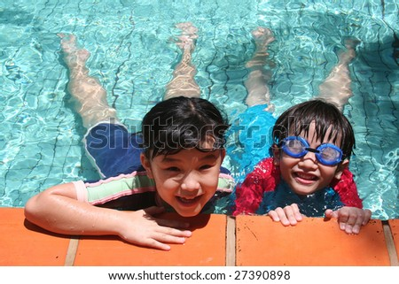 Kids with goggles in the pool on sunny day - stock photo