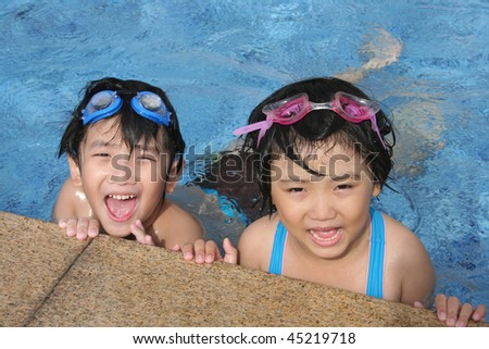 Kids with goggles playing happily in the pool - stock photo