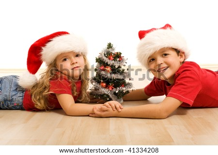 Kids with small decorated tree and christmas hats laying on the floor - isolated - stock photo