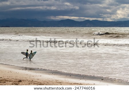 kids with surfboards running to the ocean - stock photo