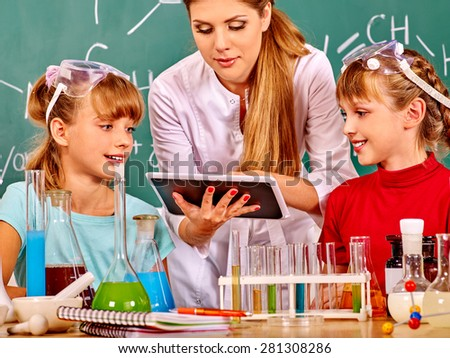 Kids with teacher  holding tablet pc in chemistry class. - stock photo