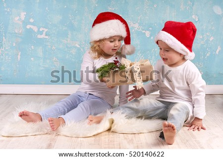 Kids with their christmas presents sitting on the floor