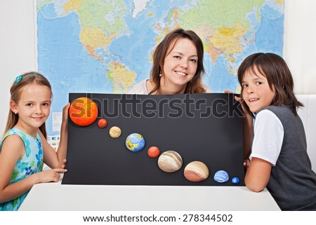 Kids with their science teacher showing their home project - planets of the solar system - stock photo