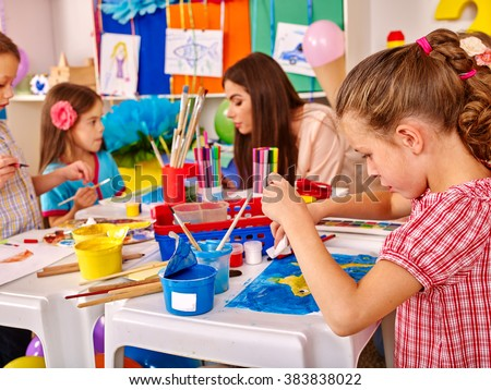 Kids with young beautiful teacher woman painting on paper at big table together  in  kindergarten .  - stock photo