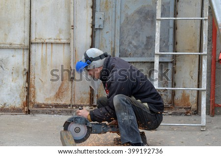 KIEV REGION, UKRAINE - MAR 31, 2016: Worker on the reconstruction old garage in countryside .March 31, 2016 Kiev Region, Ukraine