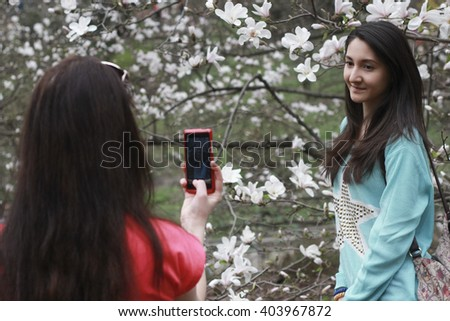 KIEV, UKRAINE - April 10, 2016: Daily life in Kiev. People photographed with magnolia flower in a botanical garden named after Academician Alexander Fomin. - stock photo