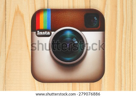 KIEV, UKRAINE - APRIL 30, 2015:Instagram logotype camera printed on paper and placed on wooden background. Instagram is an online mobile photo-sharing, video-sharing service. - stock photo