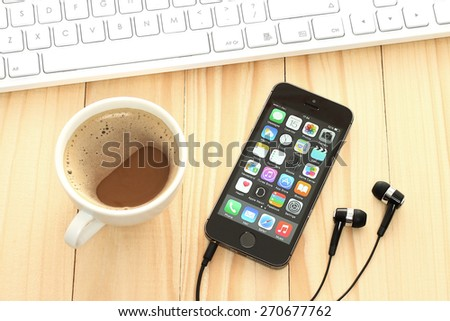 KIEV, UKRAINE - APRIL 15, 2015:iPhone 5s Space Gray with coffee and keyboard on wooden background. iPhone is a line of smartphones designed by Apple Inc. - stock photo