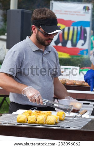 KIEV, UKRAINE - AUGUST 08, 2014:A man cooking sweet corn on a grill on a beer festival in Kyiv, Ukraine