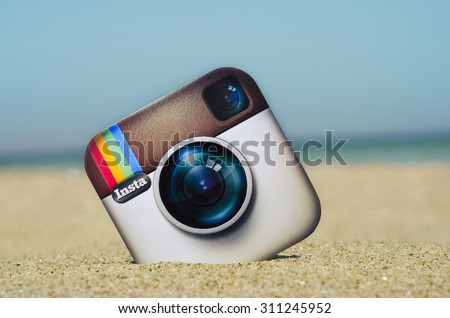 KIEV, UKRAINE - AUGUST 10, 2015: Instagram logotype camera printed on paper and placed in the sand against the sea. Instagram - free application for sharing photos and videos. - stock photo