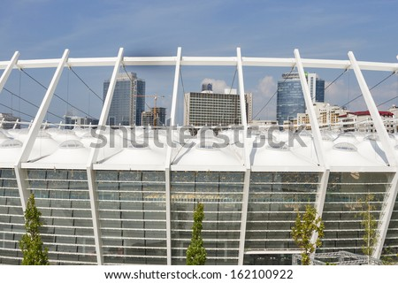 KIEV, UKRAINE - AUGUST 07: Modern Olympic National Sports Complex futuristic architecture with cityscape on August 07, 2013 in Kiev, Ukraine. It hosted the final of Euro 2012 Football Championship. - stock photo
