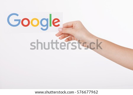 Kiev, Ukraine - August 22, 2016: Woman hands holding colorful Google logotype printed on paper on grey background. Google is USA multinational corporation.