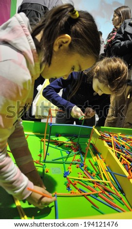 KIEV, UKRAINE - CIRCA APRIL 2014: Unknown children play with mind toys on the art and book exhibition in Arsenal museum circa April 2014 in Kiev, Ukraine