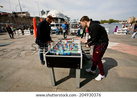 KIEV, UKRAINE - CIRCA MAY 2014: Active men have fun during foosball game on the street festival on the banks of Dnieper River on May 2014. Kiev is 8 largest city in Europe with population 3 million - stock photo
