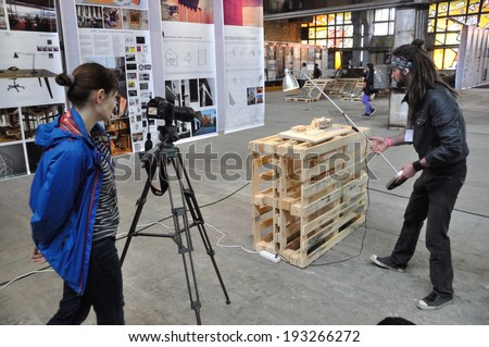 KIEV, UKRAINE - CIRCA MAY 2014: Unknown people make a movie with architectural model on the architectural �Canactions 2014� exhibition on an old factory on May 2014 in Kiev, Ukraine